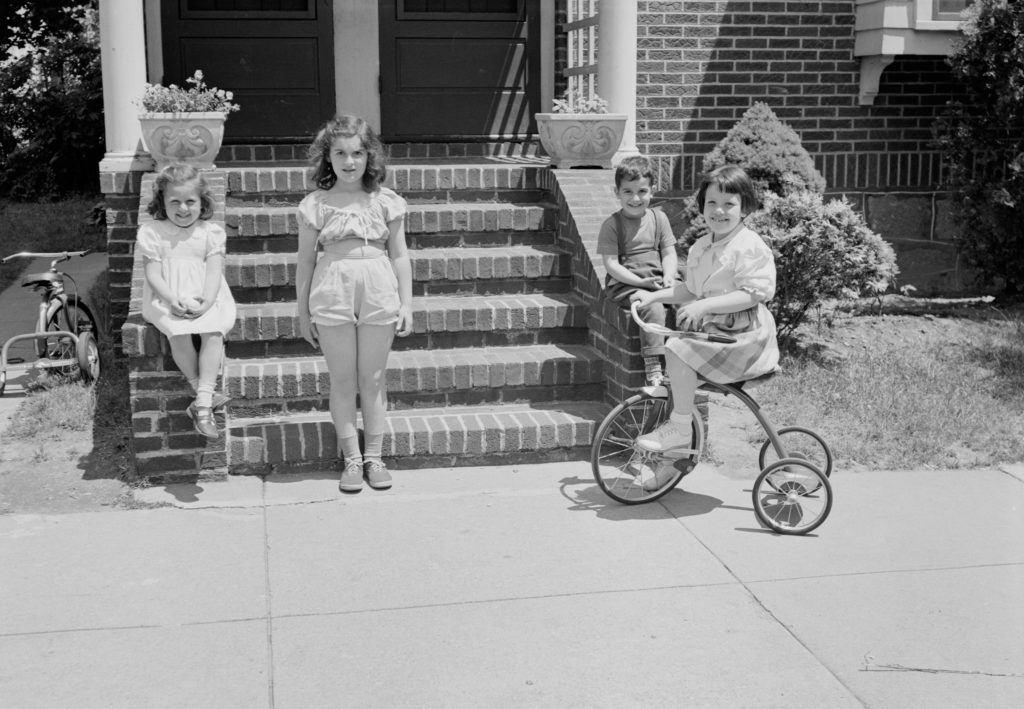 Black and white vintage picture of kids on steps and one on a tricycle.